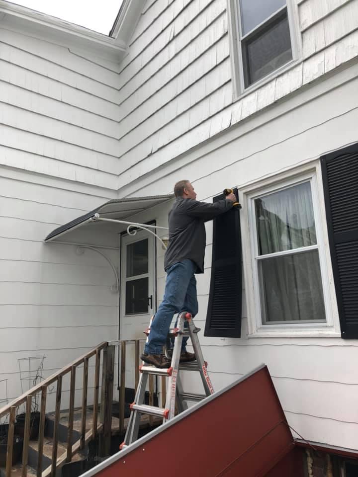 Man on ladder fixing shutter